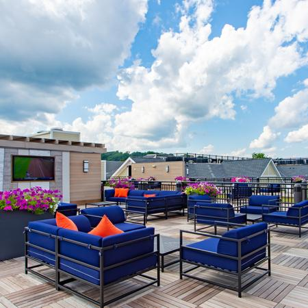 Expansive open rooftop area with outdoor television and sitting space