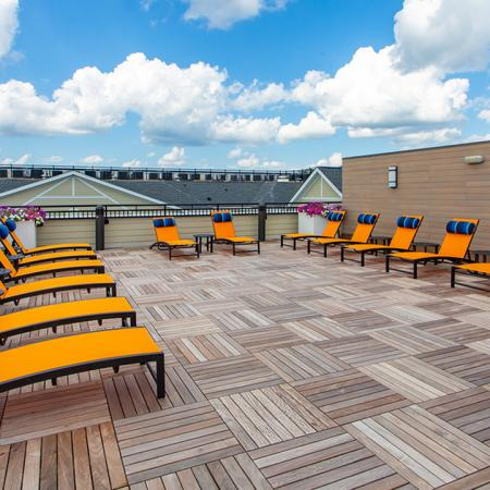 Rooftop lounging area with brightly colored chaise loungers