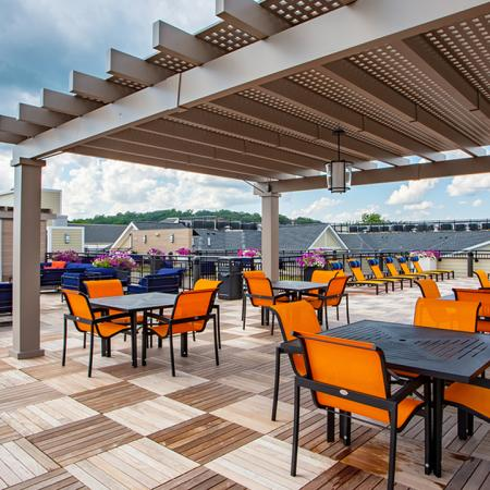 Expansive 7,000 Square Foot Rooftop Lounge with table and chairs under the pergola