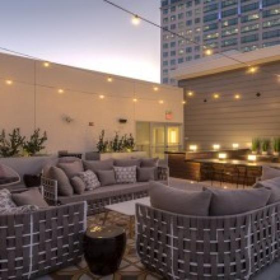 Outdoor patio space with plush seating and overhead lights