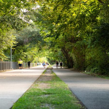Katy Trail jogging path with lush greenery and people running
