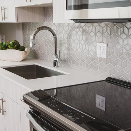 Beautiful tile back splash in kitchen with sleek glass cook top stove and large farmhouse sink