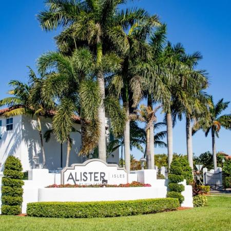 Entrance sign for Alister Isles with large palm trees