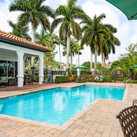Resort inspired pool featuring loungers and cabana style seating