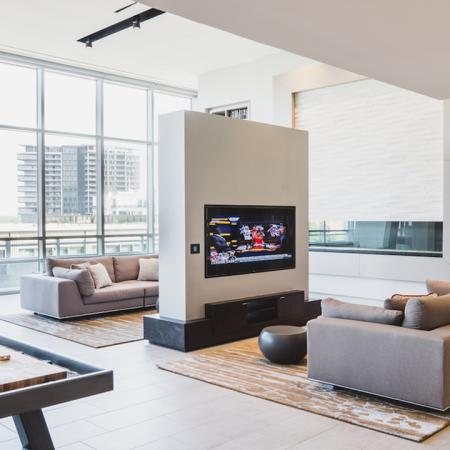 Intimate seating in resident lounge with view of wall mount television near shuffleboard table