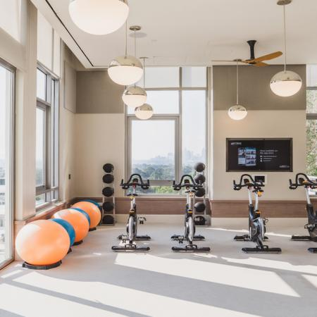 Spin bike room featuring floor to ceiling windows and instruction from wall mounted television