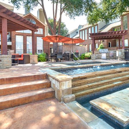 Outdoor kitchen and fireplace near pool with fountains