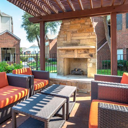 Intimate outdoor seating next to the outdoor fireplace under a pergola