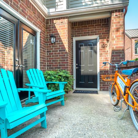 Front porch to home with brightly colored seating and community bicycle