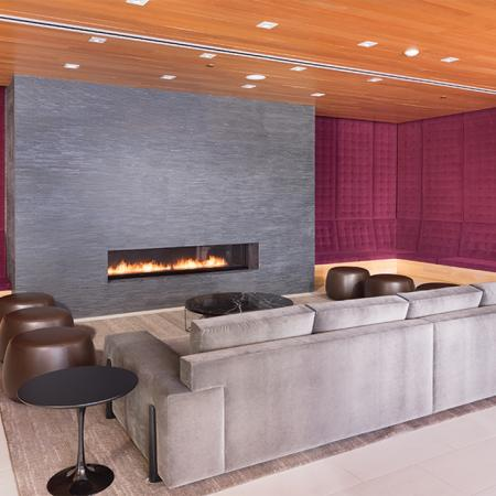 Resident lounge with velvet bench sitting reaching the ceiling along with large gas fireplace