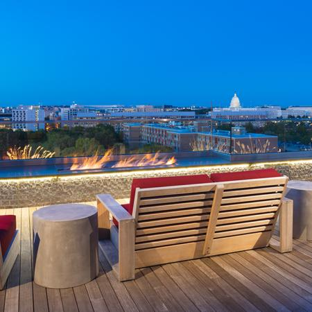 Rooftop lounge with seating and fire pits overlooking the city