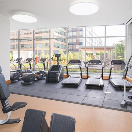 Fitness center with cardio machines overlooking a well manicured courtyard