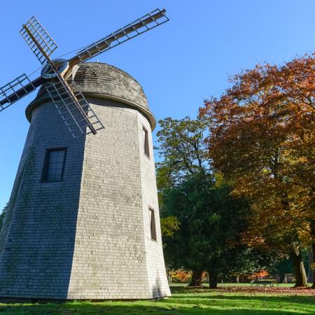 Large windmill amidst a well manicured park in the fall