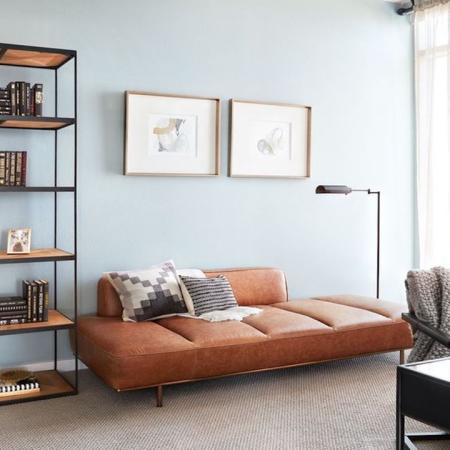 Bright Lit Living Room with Couch, Tall Book Shelves and Desk