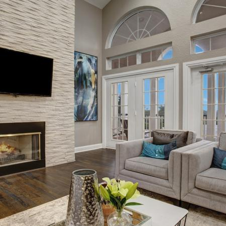 Fireside lounge with mounted TV and large decorative windows