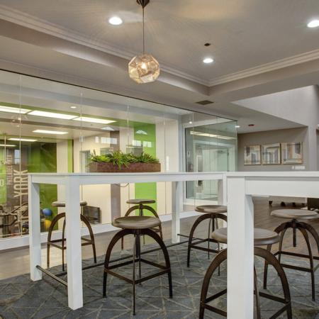Clubhouse seating featuring floor to ceiling windows with view of fitness center