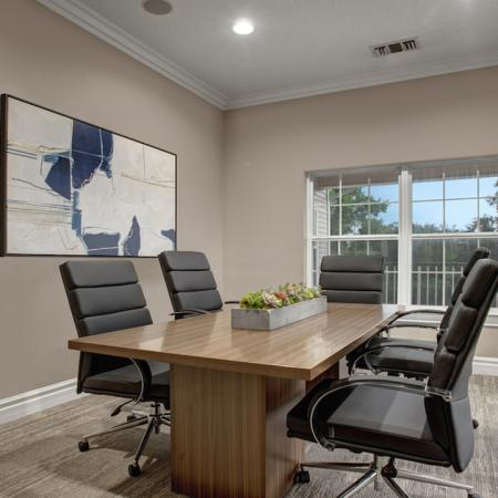 Boardroom with wooden table seating five