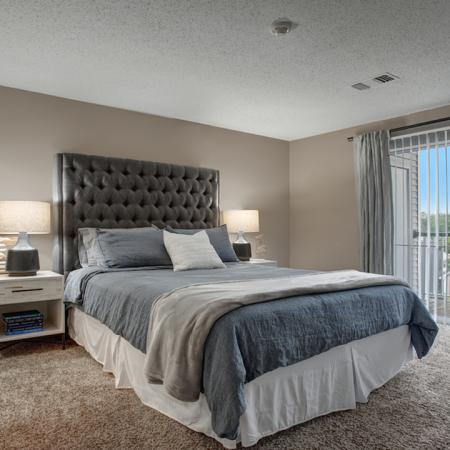 Large carpeted bedroom featuring floor to ceiling sliding glass doors