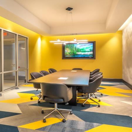 Brightly colored resident conference space with wall mounted tevevision