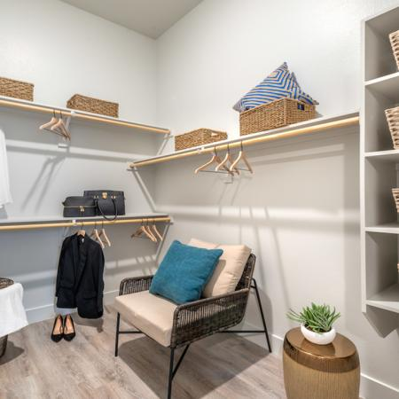 Large walk in closet with shelving and accent chair