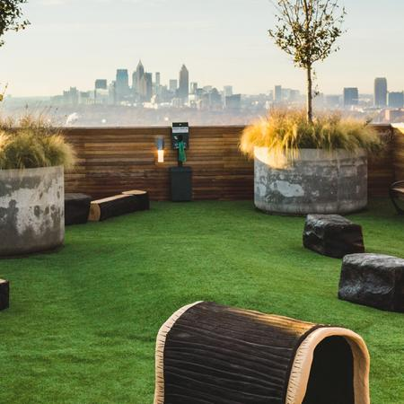 Rooftop dog park with turf grass and bench seating