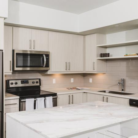 Stunning kitchens with french door stainless steel refrigerators, quartz counters, tile backsplash, and built in shelving