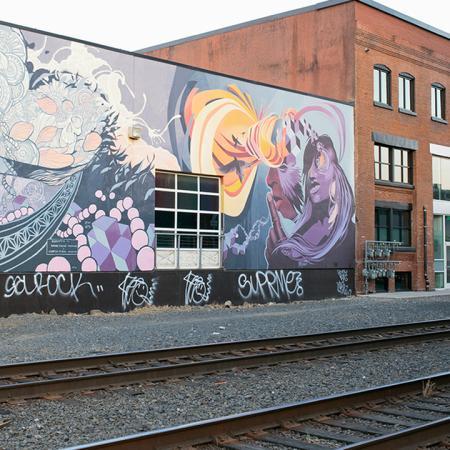 Exterior of building with mural next to railroad tracks