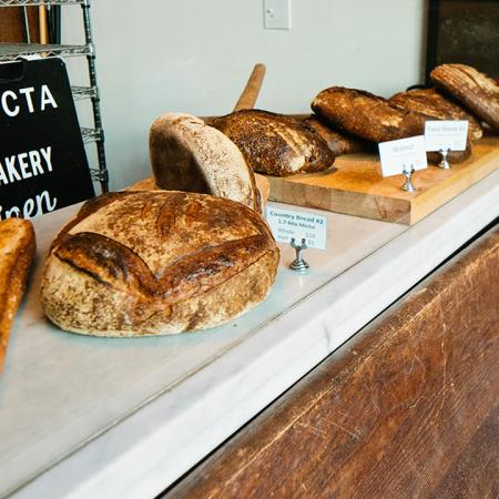 Interior of Trifecta Bakery with different breads lined up