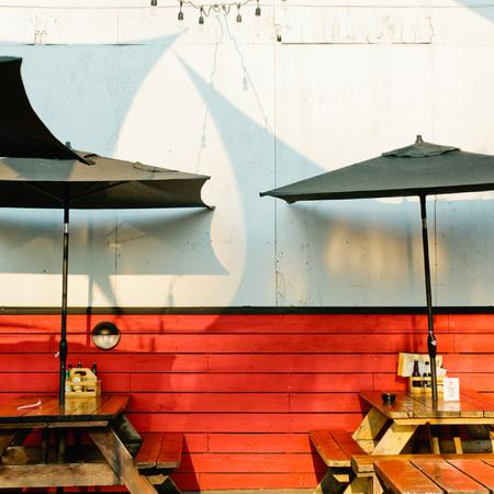 Picnic table seating with umbrellas at local establishment