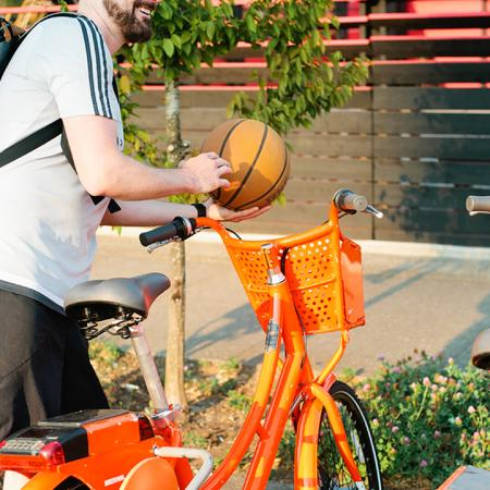 Man getting on bike with basketball