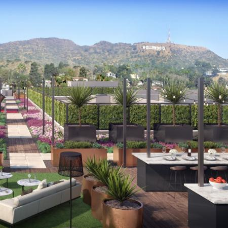 Rendering of an outdoor amenity area that includes grilling station, lounge seating, bar dining area with scenic views of the Hollywood hills