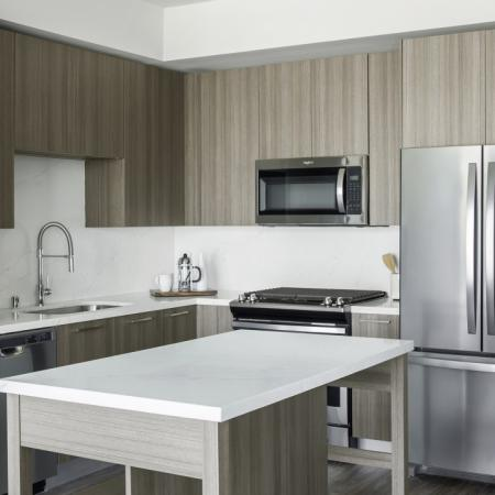 Interior kitchen with stainless steel appliances, island and upgraded grey finishes