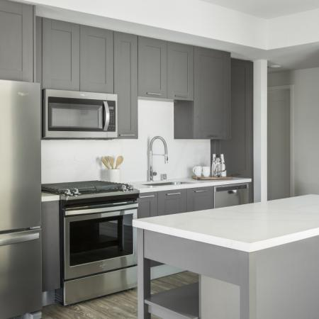 Interior Kitchen Sleek shaker grey cabinetry with stainless steel appliances and quartz countertops.