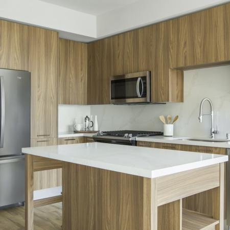 Interior kitchen with warm brown cabinetry, stainless steel appliances, and beautiful backsplash