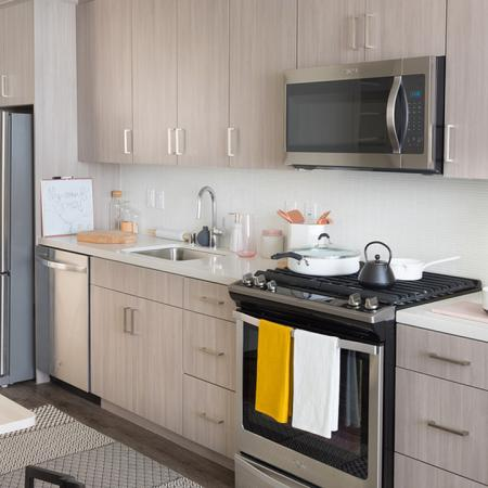 Grey finished cabinetry in open concept kitchen with stainless steel appliances