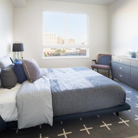 Bedroom with blue accents featuring Queen bed, full size dresser, and accent chair
