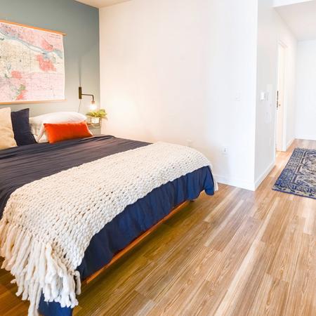 Huge bedroom space showing a queen bed and wood flooring in Portland