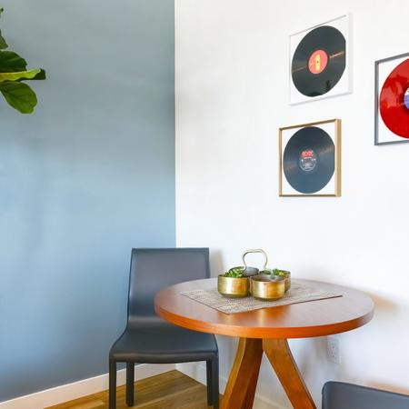 Showing small dining table area with records hung on wall.