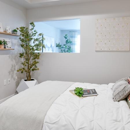 Bedroom with queen sized bed, shelves and interior window that brings light from living area