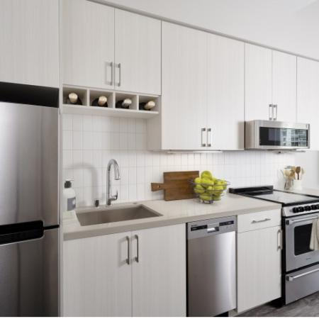 Stainless steel appliances, wine storage above stove and white cabinetry