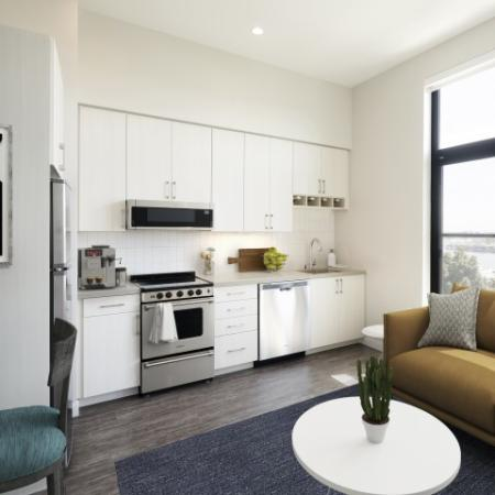 Living room with brown couch white table and peeking through to kitchen with white cabinetry and stainless steel appliances