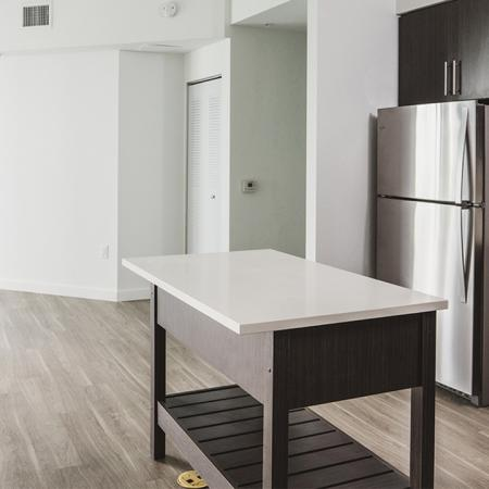 Stunning open floorplans with wood flooring, brown custom cabinetry in kitchens, tile back splash, USB ports and islands
