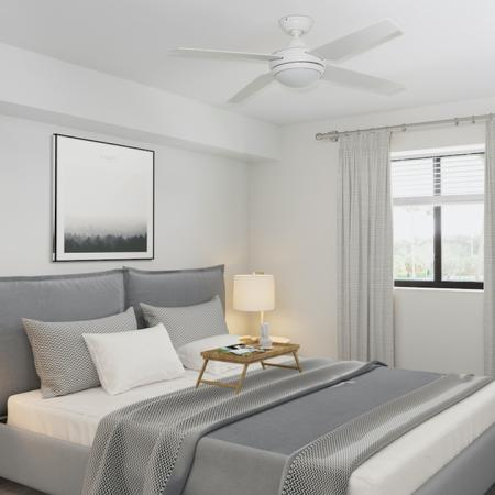 Large bedroom with wood flooring and ceiling fans