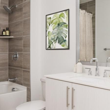 Bathroom with white cabinetry, quartz countertops, built in shelving and upscale shower head fixtures