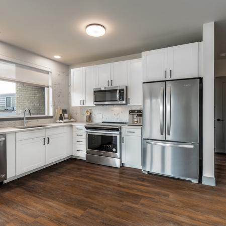 Beautiful kitchens with window, stainless steel appliances with french door refrigerators and custom white cabinetry