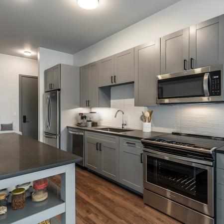 Chef-inspired kitchens with grey custom cabinetry and moveable island with ample storage and mudroom
