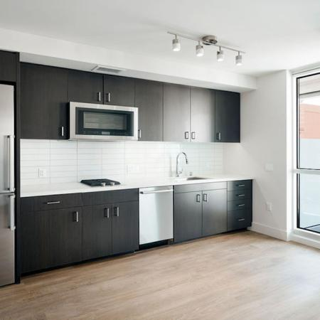Galley Kitchen with view into living area at Modera Rincon Hill apartments.