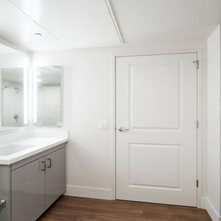 Bathroom with full-sized front loading washer dryer, backlit mirror and stunning vanities at Modera Rincon Hill apartments.