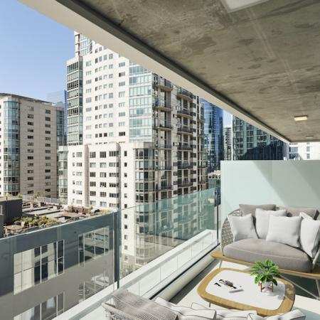 Private balcony with stunning city views and private seating area at Modera Rincon Hill apartments.