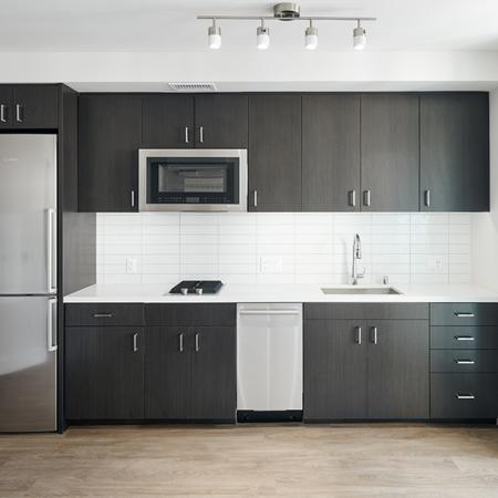 Beautiful kitchens with custom wood cabinetry, speed ovens, and stainless steel appliances in an apartment at Modera Rincon Hill.
